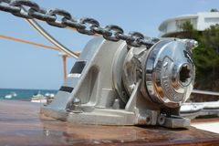 A boats winch and chain. Close up View of a boats winch on the bow Stock Photos