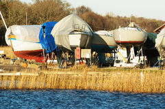 Boats in winter storage. Covered with tarps and supported by scaffoldings. Winter storage on land protects the boats from the sea ice that could otherwise cause Royalty Free Stock Photography