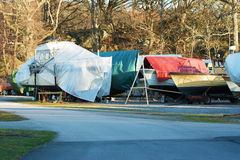 Boats in winter storage. Covered with tarps and supported by scaffoldings. Winter storage on land protects the boats from the sea ice that could otherwise cause Stock Photography