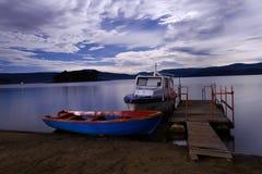 Boats. Wooden Row Boat and Motor Boat at the Bay Royalty Free Stock Photos