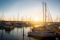 Boats and yachts docked in marina at sunset Stock Photo