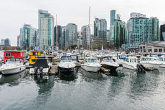 Boats and yachts with highrise buildings in Vancouver, Canada Stock Photos
