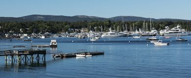 Boats and yachts moored in a harbor in Maine. Many boats and some yachts are moored in a peaceful harbor with mountains in the background in Maine Stock Images