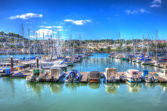 Boats and yachts moored in marina with vivid blue sky and clouds in HDR like painting Stock Image