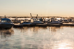 Boats and yachts moored at the port. Glittering sea surface against sunrise. Morning fog Royalty Free Stock Photos