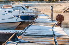 Boats and yachts moored at the port. Glittering sea surface against sunrise. Morning fog Stock Photography