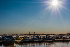 Boats and yachts moored at the port. Glittering sea surface against sunrise. Morning fog Stock Image