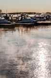 Boats and yachts moored at the port. Glittering sea surface against sunrise. Morning fog Royalty Free Stock Image
