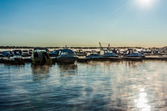 Boats and yachts moored at the port. Glittering sea surface against sunrise. Morning fog Stock Photos