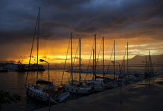 Boats and Yachts moored in port on sunset evening Stock Photos