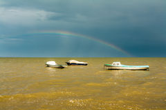 Boats in the yellow waters. Of the Azov sea and rainbow Stock Images