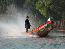 Boatsman on lake inle. A boatsman is standing in his boat, looking attentively, while the the motor makes the water splash to the back Stock Photography