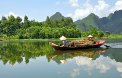 Boatwomen of Vietnam. Two boatwomen of Vietnam bringing back firewood they have gathered to the village dock Stock Image