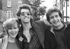Bob Geldof. (centre), Lead singer of Irish pop group The Boomtown Rats, poses with two fans prior to a performance in London, circa 1978 Royalty Free Stock Photo