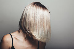Bob haircut. Model with unrecognizable face with blond shiny hair. Woman bob haircut styling Stock Images