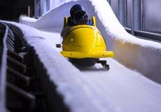 Bob sled speeding in an ice channel. A bob sled speeding in an ice channel Royalty Free Stock Photos