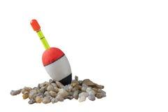 Bobber de pêche sur de petites pierres avec le fond d'isolement image libre de droits