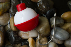 Bobber and Hook. A bobber and hook resting on stones Royalty Free Stock Photography