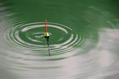 Bobber met groene golven royalty-vrije stock fotografie
