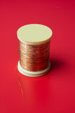Bobbin of golden thread. On a red background royalty free stock photos