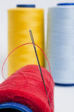 Bobbin and Needle Closeup. Red Bobbin and Needle Stuck on it Royalty Free Stock Photography
