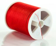 Bobbin of red sewing thread. A closeup of a single bobbin of sewing thread on a white background Stock Photo