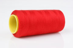 Bobbin with red thread on white background Stock Images