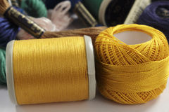 Bobbin and skein of cotton thread orange Royalty Free Stock Photography