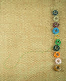 Bobbin threads line the side of burlap. Bobbin threads line the right side of a piece of burlap Stock Image