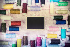 Bobbins with colorful threads on old wooden table Royalty Free Stock Image