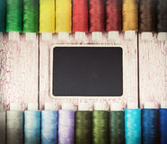 Bobbins with colorful threads on old wooden table Stock Image