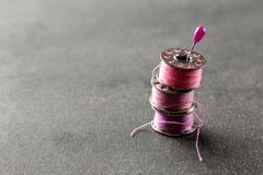 Bobbins with pink thread and a pin on a black background. stock image