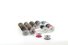Bobbins in plastic case. A range of cotton colors on bobbins in a plastic case isolated on white Royalty Free Stock Images