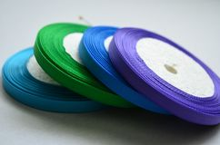 Bobbins of thin colored rep ribbon on white background stock image