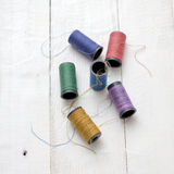 Bobbins with thread on the table Stock Photography