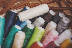 Bobbins thread in willow basket on wooden background Royalty Free Stock Photos