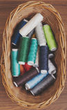 Bobbins thread in willow basket on wooden background Stock Photos