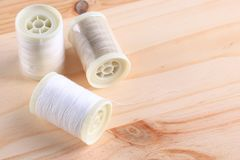 Bobbins with threads on the background of an old wooden table stock photography
