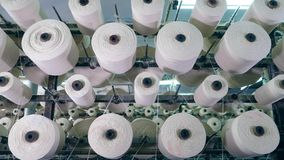Bobbins with threads rotate on a rack at a textile plant. Industrial fabric production line.