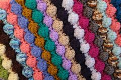 Bobble crochet stitches in diagonal stripes background texture. Bobble crochet stitches in diagonal stripes, multi-coloured yarn as abstract background texture Stock Photography