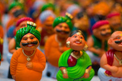 Bobble heads of indian men and women. Bobble heads of caricatures of indian men with moustaches and turbans and women in a saree Royalty Free Stock Photos