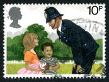 Bobby on the Beat UK Postage Stamp. GREAT BRITAIN - CIRCA 1979: A used postage stamp from the UK, depicting an illustration of a Policeman talking to two Royalty Free Stock Image
