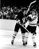 Bobby Clarke and Peter McNabb battle (NHL Hockey). Former Philadelphia Flyers superstar Bobby Clarke (16) and Boston Bruins star Peter McNabb (8) battle on the stock photos