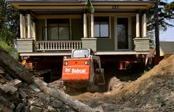 Bobcat excavator moves earth from under a jacked up house