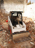 Bobcat Skid Loader in Derelict Building. A bobcat skid steer loader in a partially demolished derelict old Italian farm building Royalty Free Stock Photos