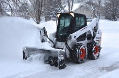 Bobcat Skid steer blows snow after a storm. MOORHEAD, MINNESOTA, March 9, 2019: The S650 Bobcat skid steer removing driveway snow is headquartered in West Fargo stock photos