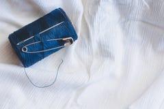 Bobina blu del filo con l'ago di cucito e perno sul panno di cotone bianco fotografia stock