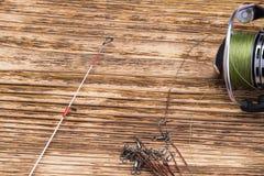 Bobina con la linea di pesca dalle bugie della canna da pesca su un fondo bruciato di legno fotografia stock libera da diritti