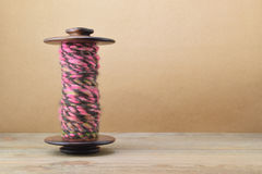 A bobina da roda de giro com mão cor-de-rosa e marrom girou o fio Fotografia de Stock Royalty Free