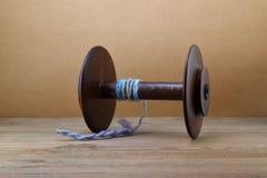 Bobina de madeira da roda de giro com um líder do fio usado para unir a vagabundagem ao girar contra um fundo do papel marrom fotos de stock royalty free